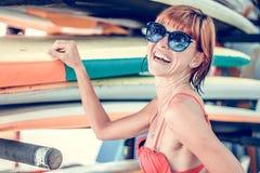Muchacha atractiva joven en traje de baño rojo - persona que practica surf con el tablero de resaca que presenta en la playa del  Fotos de archivo
