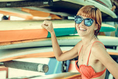 Muchacha atractiva joven en traje de baño rojo - persona que practica surf con el tablero de resaca que presenta en la playa del  Fotografía de archivo