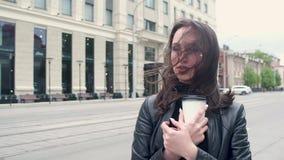 Muchacha atractiva joven en una chaqueta de cuero negra y soportes de los vidrios en el viento frío con café en su mano endereza  almacen de video