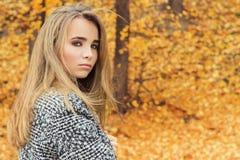 Muchacha atractiva joven encantadora hermosa con los ojos azules grandes, con el pelo oscuro largo en el bosque del otoño en capa Imágenes de archivo libres de regalías