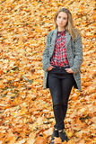 Muchacha atractiva joven encantadora hermosa con los ojos azules grandes, con el pelo oscuro largo en el bosque del otoño en capa Foto de archivo