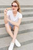 Muchacha atractiva joven hermosa en gafas de sol que come el helado en la escalera y que lame los labios regordetes al día calien fotos de archivo libres de regalías
