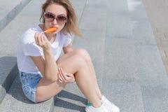 Muchacha atractiva joven hermosa que se sienta en las escaleras en pantalones cortos y gafas de sol y que come un helado delicios foto de archivo