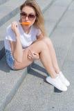 Muchacha atractiva joven hermosa que se sienta en las escaleras en pantalones cortos y gafas de sol y que come un helado delicios foto de archivo libre de regalías