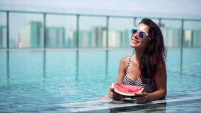 Muchacha atractiva joven que come la sandía en la piscina almacen de metraje de vídeo