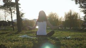 Muchacha atractiva joven que hace ejercicios, poniendo y estirando en una estera de la yoga en parque Concepto activo sano metrajes