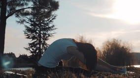 Muchacha atractiva joven que hace ejercicios, poniendo y estirando en una estera de la yoga en parque Concepto activo sano almacen de video