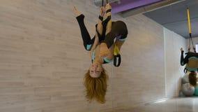 Muchacha atractiva joven que hace estirar, colgante al revés en el gimnasio metrajes