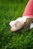 Muchacha atractiva joven que miente en la hierba Foto de archivo