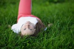 Muchacha atractiva joven que miente en la hierba y que mira a la cámara Fotografía de archivo libre de regalías