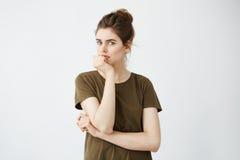 Muchacha atractiva joven que piensa con la mano en la barbilla que mira la cámara sobre el fondo blanco Imagen de archivo libre de regalías