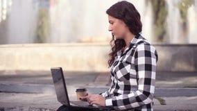Muchacha atractiva joven que trabaja en un ordenador móvil con una mirada seria que se sienta en el pórtico en la ciudad almacen de video