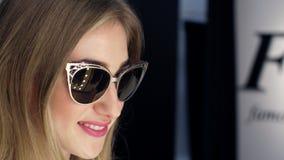 Muchacha atractiva, mujer rubia alta, hermosa que intenta en las gafas de sol en una tienda elegante, boutique y admirándose en f almacen de metraje de vídeo