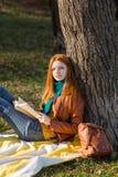 Muchacha atractiva pensativa del pelirrojo que se relaja en parque del otoño Foto de archivo