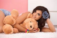 Muchacha atractiva que abraza la sonrisa del oso de peluche Imagen de archivo libre de regalías
