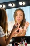 Muchacha atractiva que aplica su maquillaje en un espejo Imágenes de archivo libres de regalías