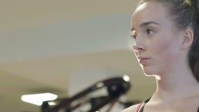 Muchacha atractiva que bebe una bebida de la sacudida de la proteína y que sonríe en el gimnasio almacen de video