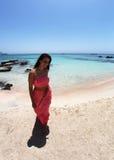 Muchacha atractiva que camina en la playa en un vestido coralino Imágenes de archivo libres de regalías
