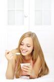 Muchacha atractiva que come el yogur Imagenes de archivo