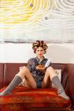 Muchacha atractiva que come los espaguetis en el sofá Imágenes de archivo libres de regalías