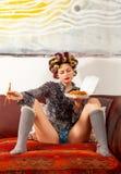 Muchacha atractiva que come los espaguetis en el sofá Foto de archivo