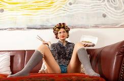 Muchacha atractiva que come los espaguetis en el sofá Imagen de archivo