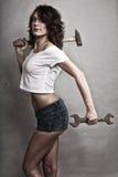 Muchacha atractiva que detiene a la llave inglesa del martillo y de la llave Imagen de archivo libre de regalías