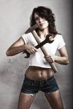 Muchacha atractiva que detiene a la llave inglesa del martillo y de la llave Foto de archivo libre de regalías