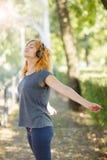 Muchacha atractiva que disfruta de música en los auriculares que presentan en un fondo del parque Concepto de la relajación Copie Fotos de archivo