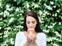 Muchacha atractiva que goza de una taza de café en la naturaleza Imagen de archivo