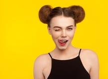 Muchacha atractiva que guiña lamiendo los labios que llevan el top Imagen de archivo libre de regalías