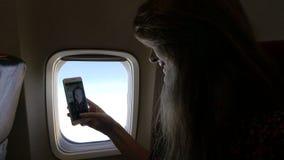 Muchacha atractiva que hace el selfie en el avión cerca de la ventana HD almacen de video