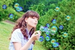 Muchacha atractiva que infla burbujas de jabón coloridas Foto de archivo libre de regalías