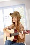 Muchacha atractiva que juega la sonrisa de la guitarra Foto de archivo