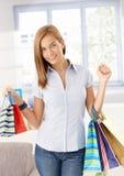 Muchacha atractiva que llega de la sonrisa de las compras Foto de archivo libre de regalías
