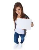 Muchacha atractiva que lleva a cabo la muestra en blanco Foto de archivo libre de regalías