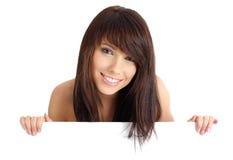 Muchacha atractiva que lleva a cabo a una tarjeta en blanco. Foto de archivo