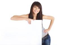 Muchacha atractiva que lleva a cabo a una tarjeta en blanco. Fotos de archivo libres de regalías