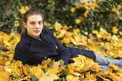 Muchacha atractiva que miente en hojas caidas del otoño Foto de archivo libre de regalías