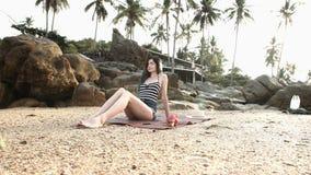Muchacha atractiva que miente en la playa en un traje de baño y pantalones cortos en el sol almacen de metraje de vídeo
