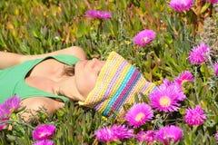 Muchacha atractiva que miente en un campo con flo colorido Foto de archivo