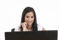 muchacha atractiva que mira la computadora portátil Fotos de archivo