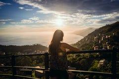 Muchacha atractiva que mira una puesta del sol hermosa Imagenes de archivo