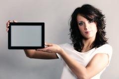 Muchacha atractiva que muestra el espacio de la copia en panel táctil de la tableta Foto de archivo