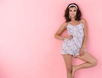Muchacha atractiva que presenta sobre la pared rosada Imagenes de archivo