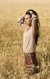Muchacha atractiva que se coloca en campo de trigo Imagen de archivo