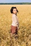 Muchacha atractiva que se coloca en campo de trigo Fotos de archivo