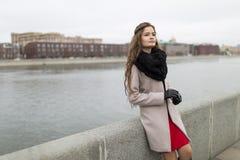 Muchacha atractiva que se coloca en la costa en la caída Muchacha en una capa negra, una bufanda y un vestido rojo contra un ciel Imagen de archivo
