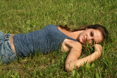 Muchacha atractiva que se reclina sobre hierba Imagen de archivo