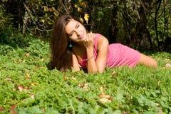 Muchacha atractiva que se reclina sobre hierba Foto de archivo libre de regalías